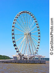 Ferris wheel on the water edge. National harbor Ferris wheel in a bright sunny day.