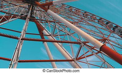 Ferris Wheel Rotates against the Sky in Summer Day. Rotating Ferris wheel with cabins or capsules and center part. Concept of lifestyle, fun, growth, relax. Batumi, Georgia. 4K.