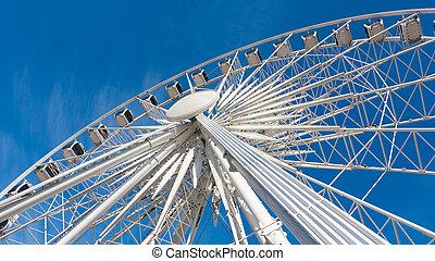 Ferris wheel rotating on blue sky background.