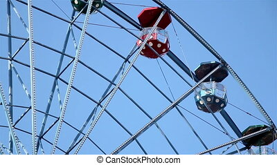 Ferris wheel slowly moving under the blue sky