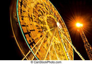 ferris wheel spinning at fairground at night