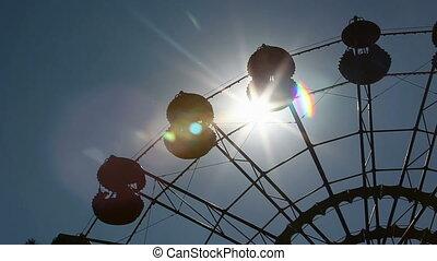 Ferris wheel over sun