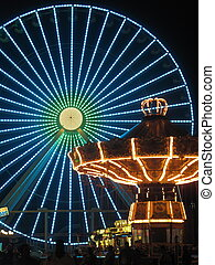 Ferris Wheel and Carousel in Amusement Park at Night