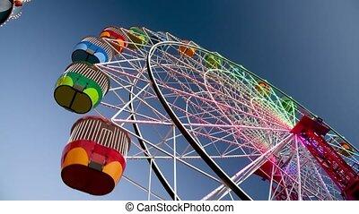 Ferris Wheel upwardview at sunset, amusement park concept Slow motion.