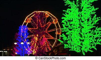 Ferris Wheel With Bright Illumination Spinning At Night