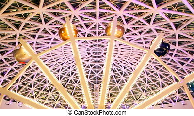 ferris wheel with flashing lights under arch of roof at nightclub