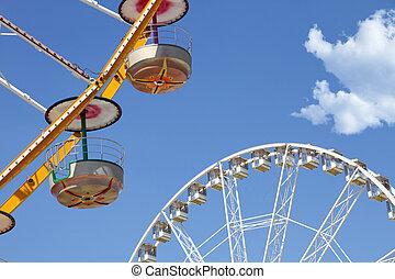 Ferris wheels in an amusement park against blue sky