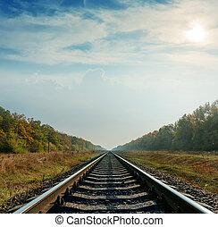 ferrocarril, primer plano, va, a, horizonte, debajo, cielo nublado, con, sol