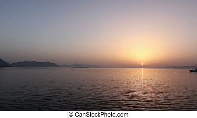 Ferry boat is in transport on early dawn, passing over sea at sunrise
