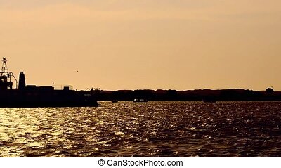 Ferry boat on sunset crossing the river.