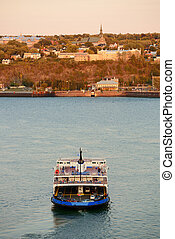 Ferry boat in river in Quebec City at sunset.