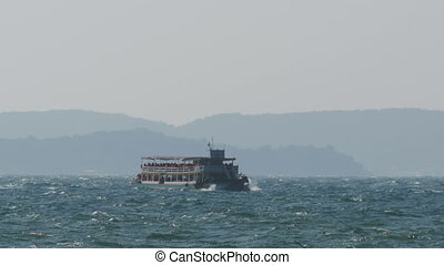 Ferry Boat with Tourists Sails on Storm Waves in the Sea....