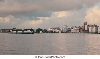 Ferry-Catamaran Sails on a Background of the City
