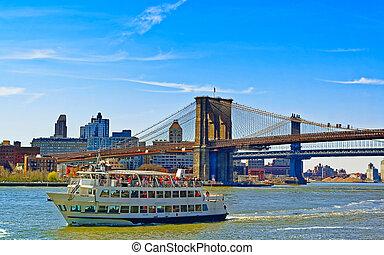 Ferry near Brooklyn bridge and Manhattan bridge over East River reflex
