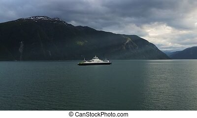 Ferry ship with passengers on Norwegian fjord. Sun rays...