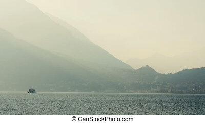 Ferry swim in the lake, contrasting the evening lighting. Lake Como, Italy.