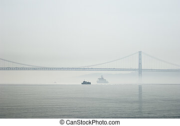 Ferrys crossing the Tagus river in a foggy morning
