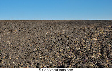 fertile, plowed soil of an agricultural field against blue sky