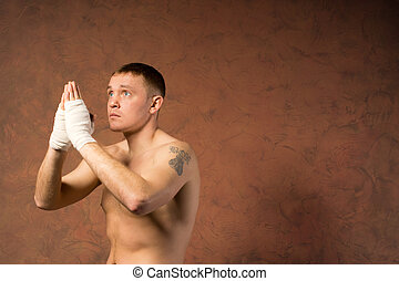 Fervent young boxer praying for victory