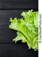 Fesh green lettuce salad organic leaves, on black wooden table