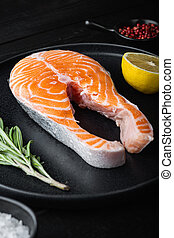 Fesh raw salmon fillet with herbs, on black wooden surface.