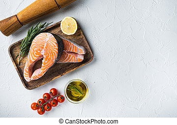 Fesh raw salmon fillet with herbs, over white background, top view with space for text.