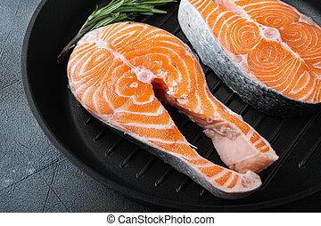 Fesh raw trout fillet on grill skillet, over grey background.