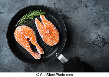 Fesh raw trout fillet on grill skillet, over grey background, top view with space for text.