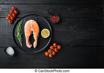 Fesh raw trout fillet with herbs, on black wooden surface, top view with space for text.