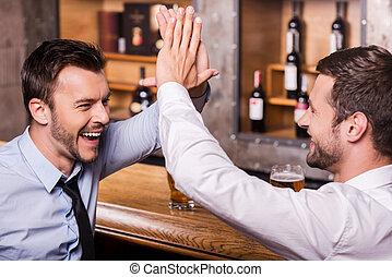 festeggiare, successo, insieme., due, allegro, giovani uomini, in, camicia cravatta, parlando, altro, e, gesturing, mentre, bere, birra, a, il, sbarra contraddice