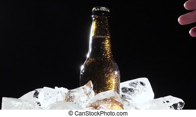 Festival, a man takes out a bottle of beer with ice. Black background. Close up. Slow motion
