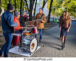 Festival music band. Friends playing on instruments city autumn park.