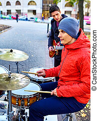 Festival music band. Friends playing on percussion instruments city outdoor.
