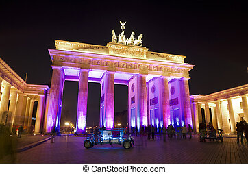 festival of lights at brandenburger tor at night with blurred people