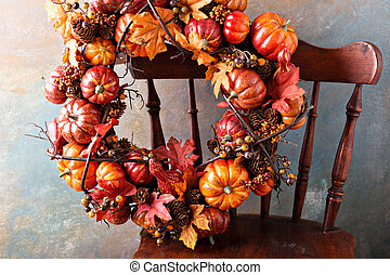 Festive autumn wreath with pumpkin and fall leaves