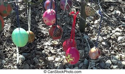 Festive background of rocks painted Easter eggs branches tree