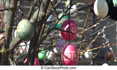 Festive background People decorate painted Easter eggs branches tree. Natural light. Arts and decoration