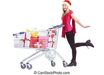 Festive blonde pushing trolley full of gifts