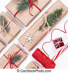Festive boxes as Christmas present with ribbon bow and fir tree branch on white background wrapped in craft paper