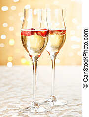 Festive champagne flutes filled with sparkling wine and floating strawberries with a backdrop bokeh of romantic twinkling party lights