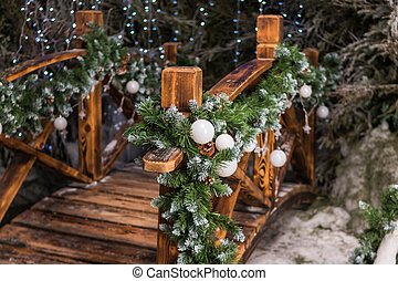 Festive Christmas decor near the house. Street decoration for winter holidays. Fir branches with white Christmas balls ornate the wooden bridge in the garden. Concept Happy Christmas