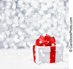 Festive Christmas gift with a large ornamental red ribbon and bow in falling snow with a bokeh and copyspace