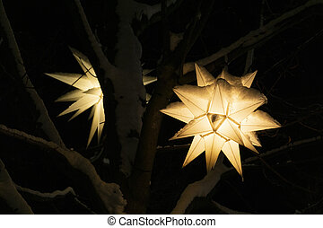 Festive Christmas glowing lantern on a tree in the shape of a star. Winter decorations in the snow