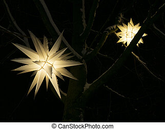 Festive Christmas tree lantern in the shape of a star glowing in the night. Winter decorations in the snow