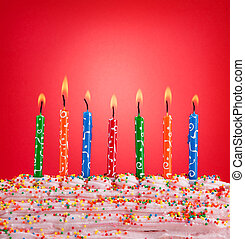 Festive concept. Happy birthday candles on red background.
