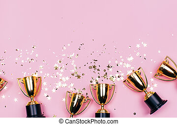 Golden winner cups with sparkles on a pink background with copy space. Festive concept. Flat lay style.