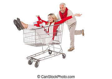 Festive couple messing about in shopping trolley on white...