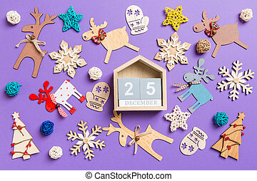 Festive decorations and toys on purple background. Top view of wooden calendar. The twenty fifth of December. Merry Christmas concept