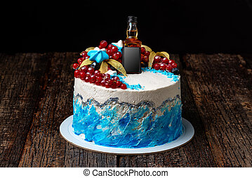 Festive fruit cream cake with a bottle of cognac, on a wooden textured background.