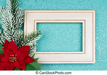 Festive greeting card for Christmas with photo frame, spruce tree branch and poinsettia on blue confetti background.